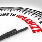 The words Time to Organize on a white clock to communicate now is the moment to get things in order, coordinate a mess, create a process or system to keep things tidy, clean and neat